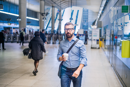 go: Hipster businessman in blue shirt with coffee cup walking in subway station Stock Photo