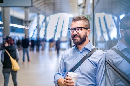 go inside: Handsome hipster businessman in blue shirt holding a coffee cup, standing on subway station
