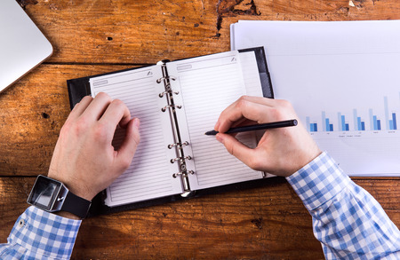 personal organizer: Hands of unrecognizable businessman writing into personal organizer. Chart graph, wooden background. Stock Photo