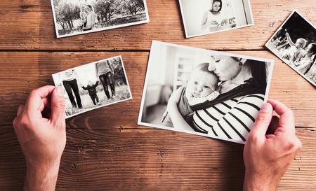 Moeders dag samenstelling. Handen van onherkenbare man met zwart-wit foto's. Studio opname op houten achtergrond.