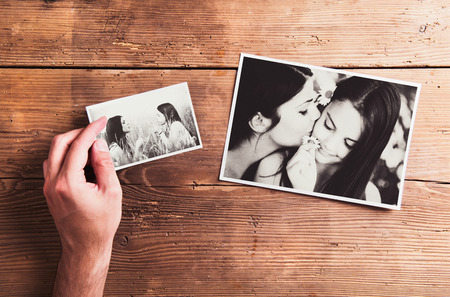 mother's hand: Mothers day composition. Hand of unrecognizable man holding  black-and-white photo. Studio shot on wooden background.