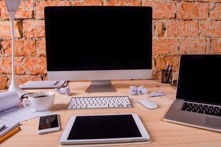 Bureau met diverse gadgets en kantoorbenodigdheden. Computer, smartphone, tablet en andere apparaten en schrijfwaren rond de werkplek.