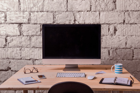 work table: Desk with various gadgets and office supplies. Computer, smart phone and stationery around the workplace. White brick wall.