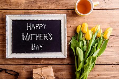 Složení matek. Obrazový rámeček s křídovou značkou, kytice žlutých tulipánů, dárek a šálek čaje. Studio shot na dřevěném pozadí.