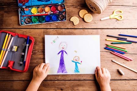 母の日の組成物。彼女の絵と彼女の母親を図面認識できない子の手。木製の背景で撮影スタジオ。
