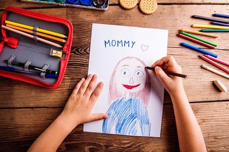 Muttertag Zusammensetzung. Hände des unerkennbaren Kinderzeichnungsbildes ihrer Mutter. Atelieraufnahme auf hölzernem Hintergrund. Standard-Bild - 55840073