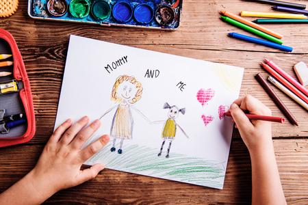 Mütter Tag Zusammensetzung. Hände von unerkennbaren Kind Zeichnung Bild von ihr und ihrer Mutter. Studioaufnahme auf Holzuntergrund. Standard-Bild - 55840119