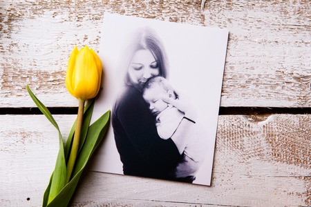 Mothers day composition. black-and-white picture of mother holding her little baby, yellow tulip. Studio shot on wooden background.