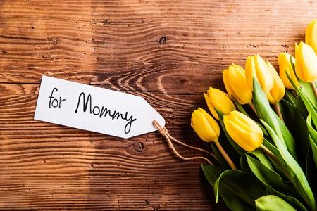 Moederdag samenstelling. Boeket gele tulpen met Voor mama tag. Studio opname op houten achtergrond. Stockfoto