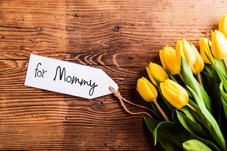 Mothers day composition. Bouquet of yellow tulips with For Mommy tag. Studio shot on wooden background.