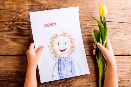 Mothers day composition. Hands of unrecognizable child holding a drawing of her mother and yellow tulip. Studio shot on wooden background.