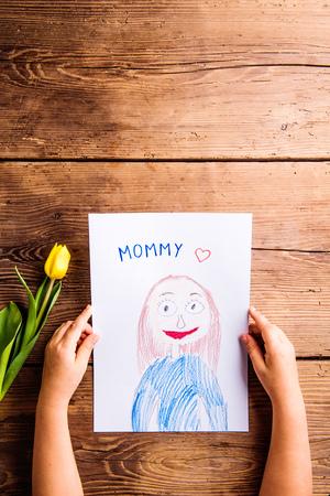Moederdag samenstelling. Handen van onherkenbaar kind met een tekening van haar moeder en gele tulp. Kopieer de ruimte. Studio schot op houten achtergrond.