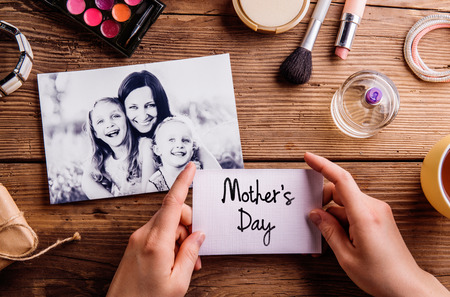 make a gift: Black-and-white picture of mother hugging her daughters and various make up products. Hands of unrecognizable woman holding Mothers Day card. Studio shot on wooden background.