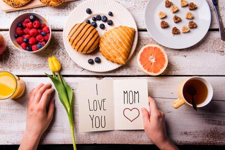 Moeders dag samenstelling. Handen van onherkenbare vrouw die wenskaart met Ik hou van je, mam, tekst. Ontbijt maaltijd. Studio opname op houten achtergrond. Stockfoto