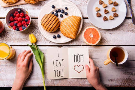 mother's hand: Mothers day composition. Hands of unrecognizable woman holding greeting card with I love you, Mom, text. Breakfast meal. Studio shot on wooden background.