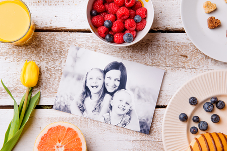 blackandwhite: Mothers day composition. Black-and-white picture of mother with her daughters and a breakfast meal. Studio shot on wooden background. Stock Photo