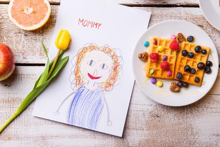 niños desayunando: Composición del día de madres. Childs dibujo de su madre, tulipán amarillo y desayuno waffles con fruta. Estudio tirado en el fondo de madera.