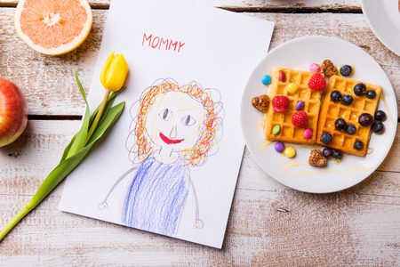 children breakfast: Mothers day composition. Childs drawing of her mother, yellow tulip and breakfast waffles with fruit. Studio shot on wooden background.
