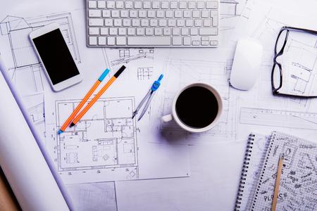 Bureau avec des gadgets et des fournitures de bureau. Le clavier d'ordinateur, le téléphone intelligent, les projets de logement et diverses choses autour du lieu de travail. Flat lay. Studio tiré sur un fond en bois blanc.