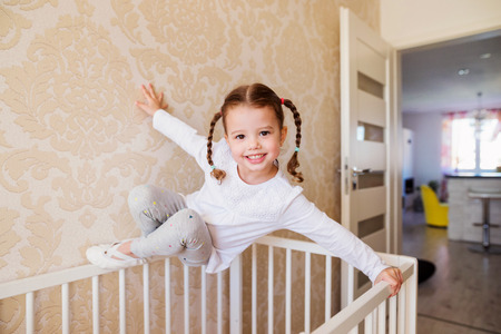 girl shoes: Cute little girl with braids hanging above white baby crib Stock Photo