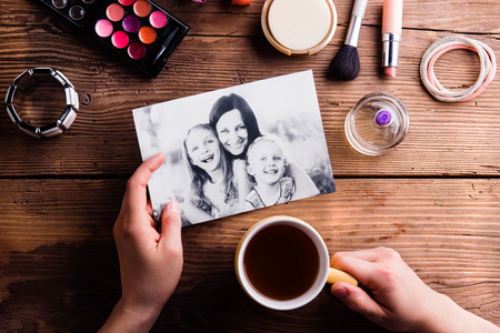 Hands of unrecognizable woman holding coffee and black-and-white picture of mother hugging her daughters and various make up products.  Studio shot on wooden background.