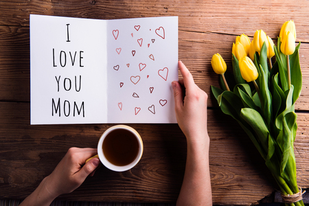 Mothers day composition. Hands of unrecognizable woman holding greeting card with I love you mom sign and coffee cup. Bouquet of yellow tulips. Studio shot on wooden background.