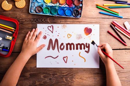 brocha de pintura: Composición del día de madres. Manos de pintura infantil irreconocible la imagen de su madre. Estudio tirado en el fondo de madera.