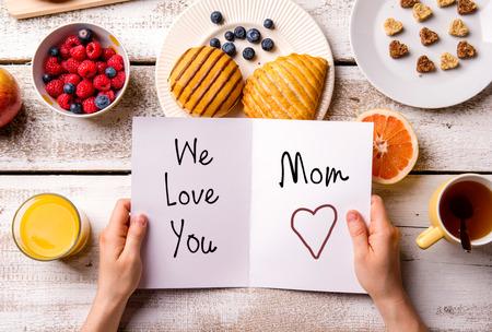 madre: Composición del día de madres. Manos de mujer irreconocible que sostiene la tarjeta de felicitación con We Love You, mamá, texto. Comida del desayuno. Estudio tirado en el fondo de madera. Foto de archivo