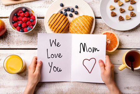 mother: Mothers day composition. Hands of unrecognizable woman holding greeting card with We love you, Mom, text. Breakfast meal. Studio shot on wooden background. Stock Photo