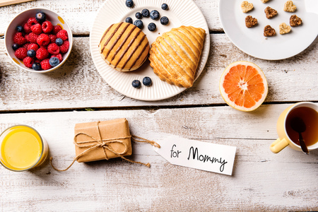 Mothers day composition. Little gift with For Mommy tag. Breakfast meal. Studio shot on wooden background. Stock Photo