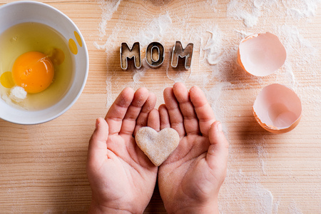 Mothers day composition. Hands of unrecognizable girl baking, holding a heart shaped cookie. Mom sign made of cookie cutters. Egg and flour. Wooden background.