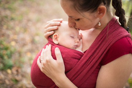 baby carrier: Mother carrying her cute baby daughter in sling, kissing her, outside in autumn nature