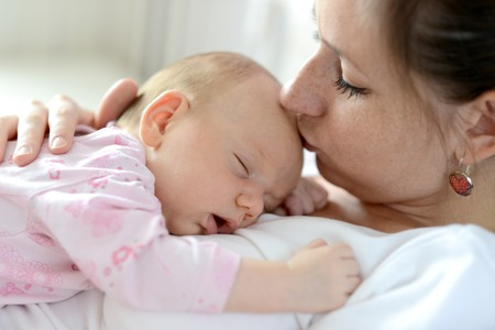 earings: Close up of young mother holding her cute baby daughter lying on her, sleeping, kissing her