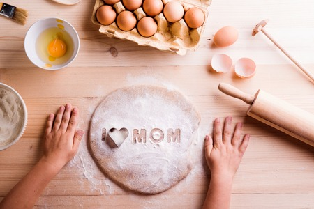 Mothers day composition. Hands of unrecognizable girl baking cookies. I love Mom sign made of flour and cookie cutter. Wooden background.