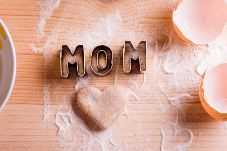 Mothers day composition. I love mom sign made of cookie cutters. Studio shot on wooden background. Stock Photo