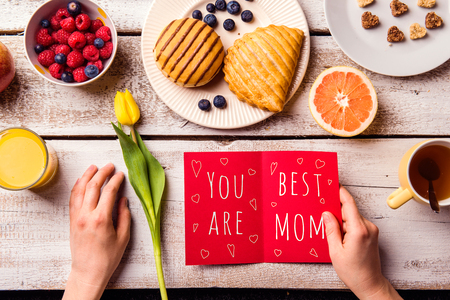 Mothers day composition. Hands of unrecognizable woman holding greeting card with You are the best mom text. Breakfast meal. Studio shot on white wooden background.