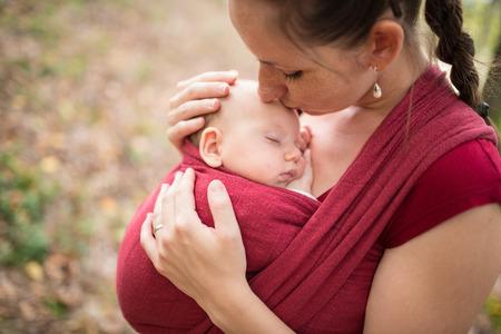 recien nacidos: Madre con su hija linda bebé en cabestrillo, besándola, afuera en la naturaleza del otoño Foto de archivo