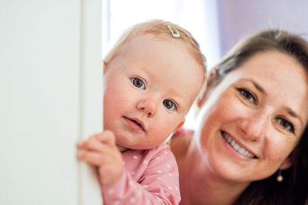 holding close: Close up of young mother holding her cute baby daughter, smiling