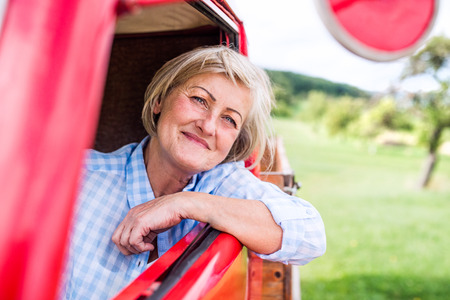 old car: Close up of senior woman in checked blue shirt inside vintage pickup truck