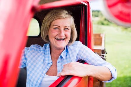Close-up van senior vrouw in gecontroleerd blauw overhemd in vintage pick-up truck