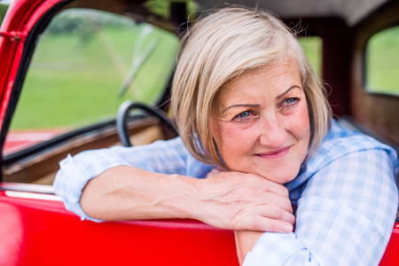 lady in red: Close up of senior woman in checked blue shirt inside vintage pickup truck