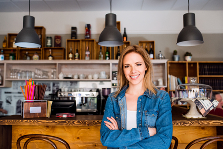 Blond woman in denim shirt standing at the bar in modern city cafe smiling Stock Photo