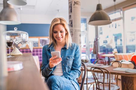 スマート携帯電話を保持近代的な都市のカフェ、バーで座っているデニム シャツの金髪女性のテキスト メッセージ