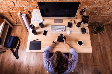 image editing: Photographer at the desk, wearing smart watch, working with camera.  Computer, smart phone and various object lens around the workplace. Stock Photo