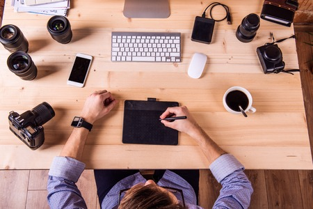image editing: Photographer at the desk, wearing smart watch, working on graphic tablet camera.  Computer, smart phone and various object lens around the workplace. Stock Photo