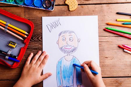 Moeders dag samenstelling. Handen van onherkenbare kindtekening foto van haar vader. Studio opname op houten achtergrond.