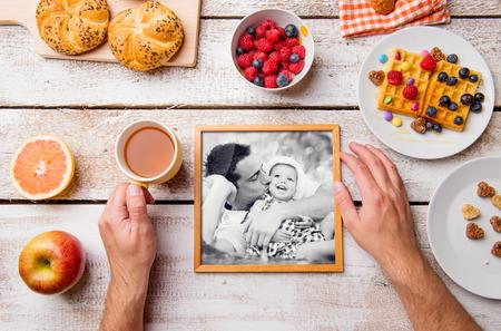 Composición del día de padres. Manos del hombre irreconocible, manteniendo la imagen en blanco y negro de él y su hija. Comida del desayuno. Foto de estudio sobre fondo blanco de madera.