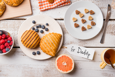 paper plates: Fathers day composition. Breakfast meal. For Daddy tag. Studio shot on white wooden background.