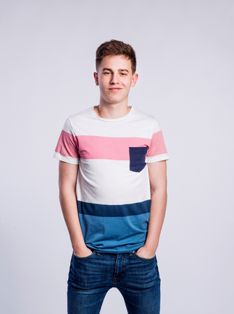 tight jeans: Teenage boy in jeans and striped t-shirt, young man, studio shot on gray background