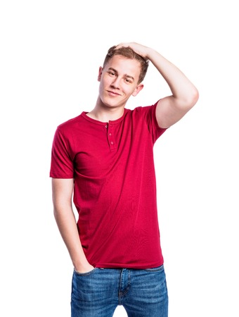 uomo rosso: Adolescente in jeans e t-shirt rossa, giovane uomo, girato in studio su sfondo bianco Archivio Fotografico